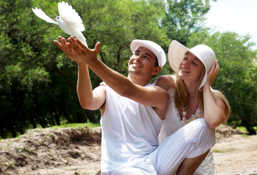 Portrait of Young Happy Couple Releasing Dove